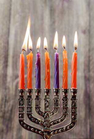 jewish holiday Hanukkah with menorah traditional and wooden dreidels spinning top . glitter overlay Stock Photo