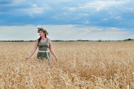 beautiful girl in a wheat field with a wreath on head Stock Photo