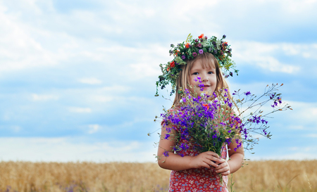 petite fille avec une couronne sur sa tête dans un champ de blé