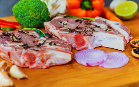 Perfect Raw Pork Neck with Spices, Ripe Tomatoes, Red Onion and Fresh Basil Leaves closeup on Wooden Cutting Board. Top View