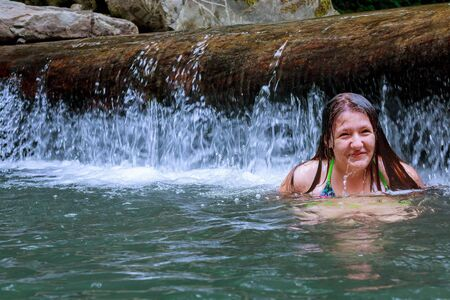 Little girl floating on the river. Bathing.