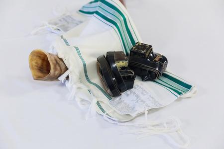 judaic: shofar horn on white prayer talit. room for text. rosh hashanah jewish holiday concept . traditional holiday symbol.