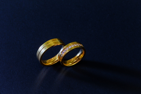 gold wedding rings with diamonds isolated on black background Stock Photo