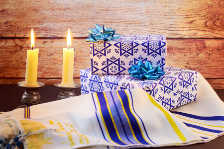 shabbat: A table set for Shabbat with lighted candles, challah bread and wine.