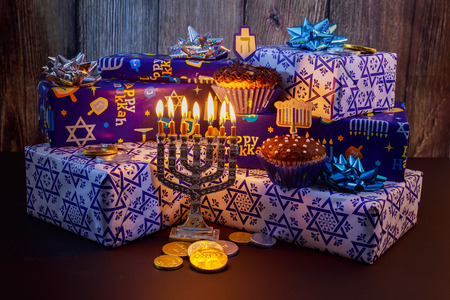 Jewish holiday Hanukkah Beautiful Chanukah decorations in blue and silver with gifts and dreidels and a Chanukiah with nine Chanukah candles for the