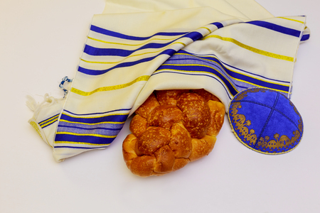 A table set for Shabbat with lighted candles, challah bread and wine.