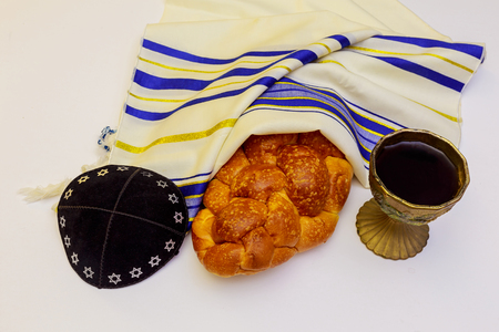 Jewish holiday Sabbath Prayer Shawl Tallit table set for Shabbat with lighted candles, challah bread and wine.