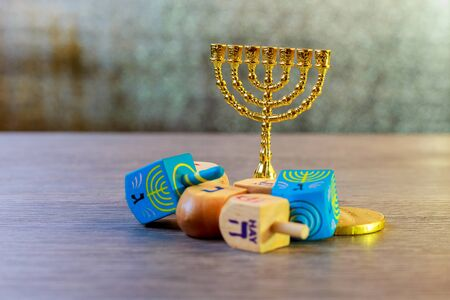 Image of jewish holiday Hanukkah with wooden dreidels colection spinning top and chocolate coins on the table
