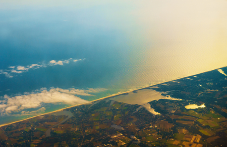 Aerial photo of the landscape and coast around the bay stretching all the way to the horizon during the sunrise in the morning with rainbow