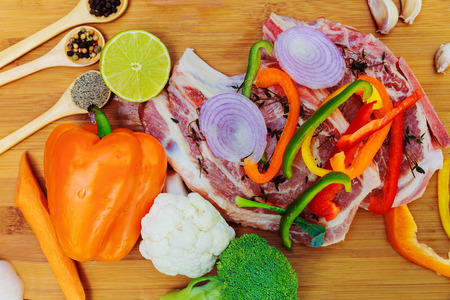 Sliced pieces of raw Meat for barbecue on wooden surface, menu cooking recipes. Food, raw steak, beef steak bbq, tomatoes, peppers, spices for cooking meat. Stok Fotoğraf