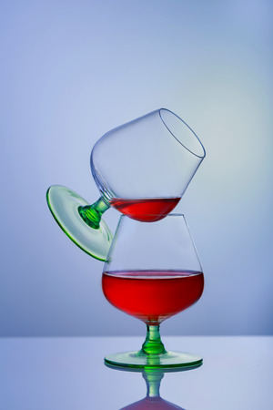 snifter: Two glasses of brandy or cognac and bottle on the table. two glasses of brandy Stock Photo
