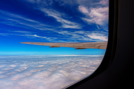 Wing of airplane flying above the clouds in the sky sky clouds flight
