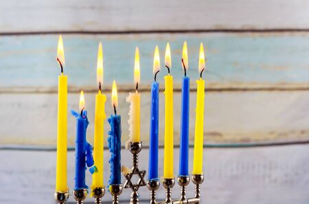 hannukah: Jewish holiday hannukah low key image of jewish holiday Hanukkah with menorah traditional Candelabra and wooden dreidels spinning top . glitter overlay