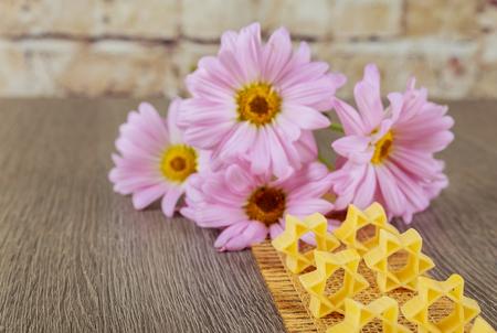 jewish food Jewish Holiday symbol pasta for broth buckwheat a pasta on a background of pink flowers Zdjęcie Seryjne