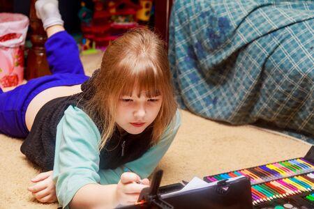 little girl draws while lies on floor. little girl draws pencils