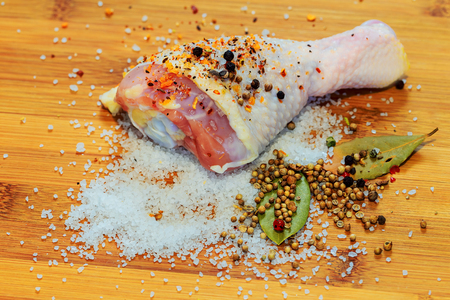 Chicken raw meat shin, drumsticks on wooden cutting board round, spices for cooking chicken drumsticks rosemary, dill, parsley, pepper and salt