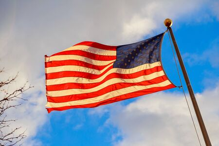 United States flag waving in the wind with beautiful sky in background Stock Photo