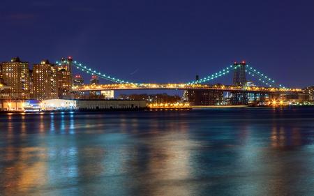 Williamsburg bridge by night, spanning the East River between Brooklyn and Manhattan Manhattan and Williamsburg bridges span across the East River between Manhattan and Brooklyn boroughs.
