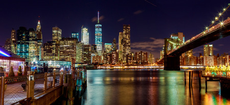 hudson: New York City Brooklyn Bridge and Manhattan skyline with skyscrapers over Hudson River illuminated with lights at dusk after sunset. Stock Photo