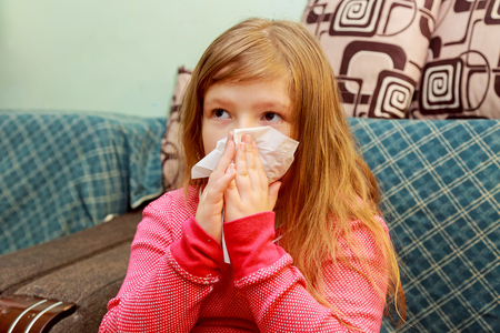 Little girl blows his nose in a paper tissue sick child wiping his nose Foto de archivo