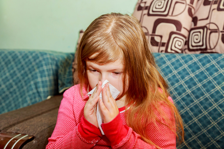 Little girl blows his nose in a paper tissue sick child wiping his nose Stock Photo