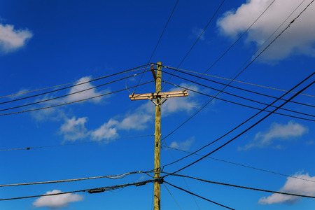 telephone poles: Old electricity post against blue sky with cloud, chaotic wire with nest on pole electric pole with wires against the sky clouds Stock Photo