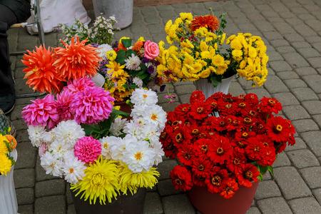 Flowers are near a flower shop on a city street. Street flower shop