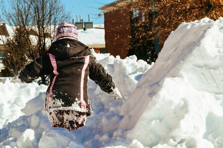 Funny little girl in a warm winter outfit, building a snow man. Kid playing outdoors in winter. Happy little kid is playing in snow, good winter weather. Child building snowman. Stock Photo