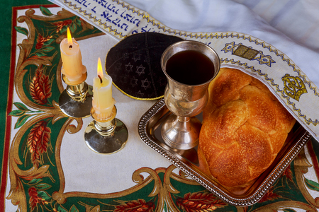 Shabbat candles in glass candlesticks i Blurred background of covered challah bread in silver tray on white tablecloth.