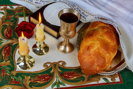 kippah: Shabbat eve table with challah bread, candles and kippah.