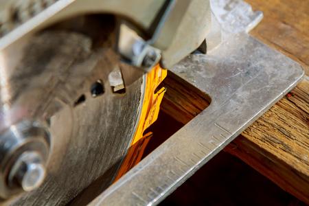 Bouwvakker met schuif zaag of cirkelsaag met schuifbalk voor het snijden van massief houten bord. Details van de bouw, renovatiewerkzaamheden