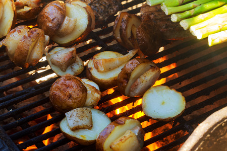 Big Slice Of Village-Style Potatoes On Hot BBQ Charcoal Grill. Flames of Fire In The Background. Tasty Snack For Outdoor Summer Barbecue Party Or Picnic. Stock Photo