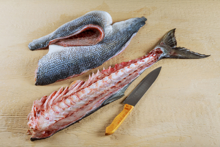 Top view of cleaning and filleting a fresh blyufish for cooking. Stock Photo