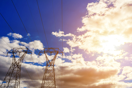electric masts against sun and cloudy sky