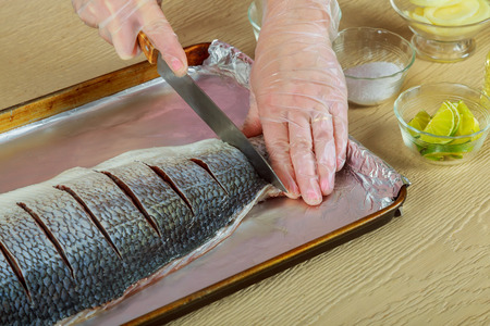 fish tail: Woman marinated fillet fish cooking raw fish on kitchen onion dish in the oven Stock Photo