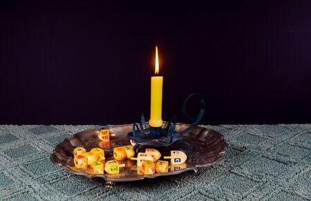 jewish holiday Hanukkahand wooden dreidels Hanukkah candle holiday Stock Photo