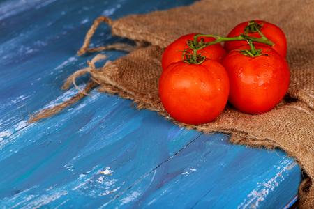 fresh, ripe cherry tomatoes on blue wooden board, horizontal Stock Photo