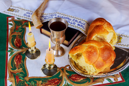 jewish home: Shabbat eve table with uncovered challah bread, candles and kippah.