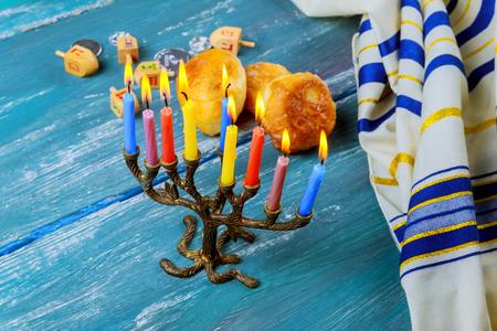 Die Menorah mit Kerzen und süßen Donuts sind traditionelle jüdische Symbole für das Chanukka-Fest.