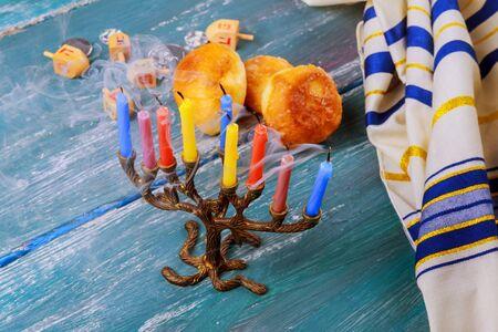 hanukka: Selective focus of the Hanukkah Jewish holiday with traditional menorah, donuts and wooden dreidel