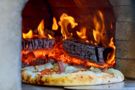 Flaming Hot Wood Fired Pizza Baking in an Oven Foto de archivo