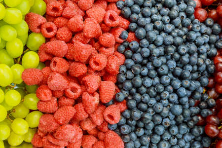 Raspberries, blackberries, blueberries a gray abstract background. Copyspace. Healthy food concept. Colorful festive still life. Loosely laid berries in different positions