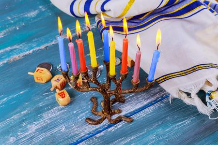 Die jüdische Menora mit Kerzen, süßen Krapfen und dreidel sind traditionelle Symbole des Chanukka-Festes Standard-Bild