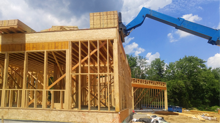 New Construction Wood Home Framing Abstract. the seeming chaos of a house frame being constructed Stock Photo