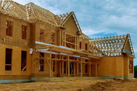 Een nieuw houten huis in aanbouw in een blauwe hemel