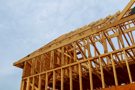 A new wooden frame on a house under construction in a blue sky
