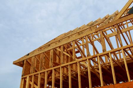 Een nieuw houten frame op een huis in aanbouw in een blauwe hemel
