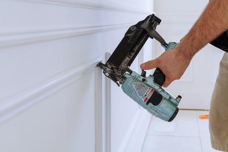 Carpenter Using A Brad Nail Gun To Complete Framing Trim Air.. Stock ...