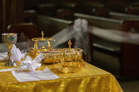 Crowns of gold for the wedding on the table in the church.