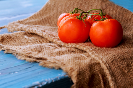 Tomatoes on vine with clipping path on cutting board , blue vintage wooden background, healthy lifestyle, cooking and market concept